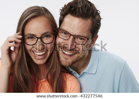 Portrait of couple wearing glasses, studio - stock photo