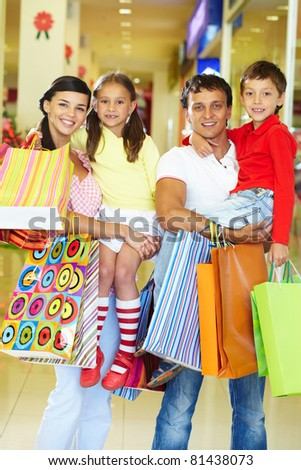 Portrait of couple with two children and shopping bags looking at camera and smiling - stock photo