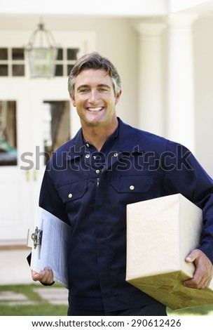 Portrait Of Courier Delivering Package - stock photo