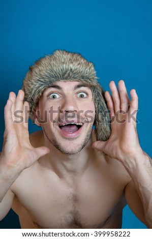 Portrait of crazy man in fur hat with emotion of surprise on blue background