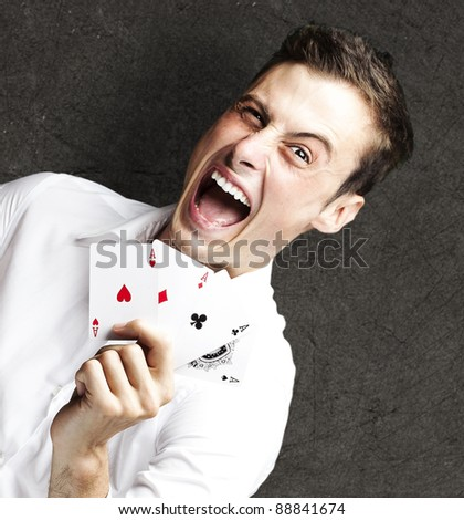 portrait of crazy man showing poker cards against a grunge background - stock photo