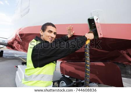 Portrait Of Crew Member Charging Airplane On Runway