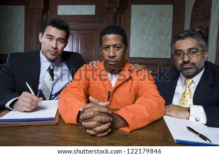 Portrait of criminal and his advocates sitting together in courtroom - stock photo