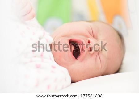 Portrait of crying newborn baby girl. - stock photo