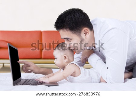 Portrait of curious male baby using laptop on the floor with his father at home - stock photo