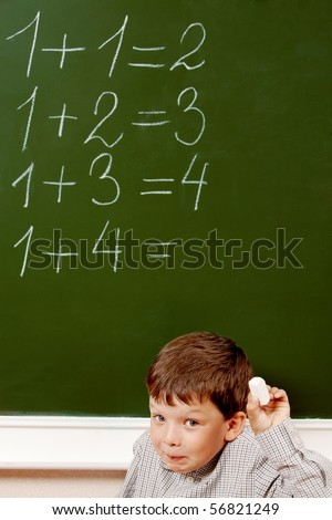 Portrait of curious schoolchild standing at blackboard with written sums on it and looking at camera - stock photo