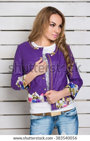 Portrait of curly blond woman in purple jacket posing near the white wooden wall - stock photo