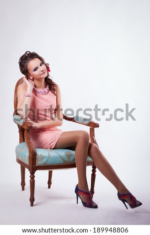 Portrait of curly brunette with purple make-up in pink dress with soutache technique decorations with flowers in her hair on a white background. Girl sitting on a chair in baroque turquoise - stock photo