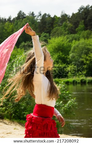 portrait of curly girl dance with pink Scarf at the river - stock photo