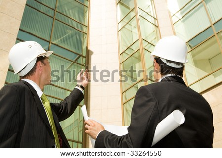 Portrait of customer showing building to architect - stock photo
