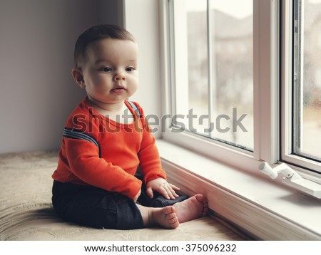 Portrait of cute adorable Caucasian baby boy girl with black eyes in orange red shirt, jeans with suspenders sitting on windowsill looking away from camera, natural window light, lifestyle - stock photo