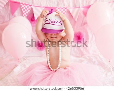 Portrait of cute adorable Caucasian baby girl with blue eyes in pink tutu skirt and pearls celebrating her first birthday with balloons looking away, cake smash first year concept - stock photo