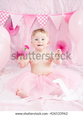 Portrait of cute adorable Caucasian baby girl with blue eyes in pink tutu skirt celebrating her first birthday with flower, gourmet cake and balloons looking in camera, cake smash first year concept - stock photo