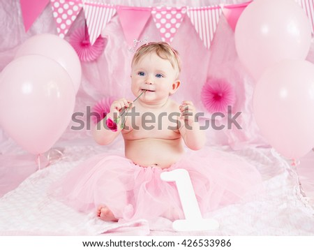Portrait of cute adorable Caucasian baby girl with blue eyes in pink tutu skirt celebrating her first birthday with flower, gourmet cake and balloons looking away, cake smash first year concept - stock photo