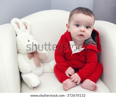 Portrait of cute adorable Caucasian smiling baby boy girl with black brown eyes in red hoodie shirt sitting in chair with toy looking directly in camera - stock photo