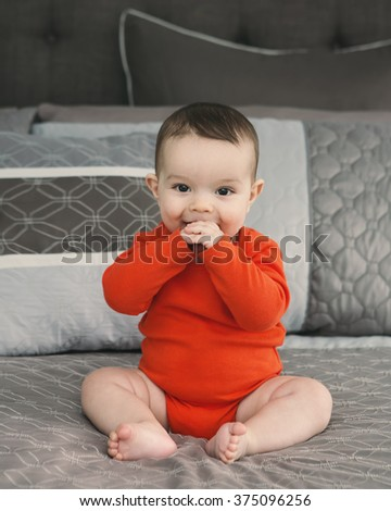 Portrait of cute adorable Caucasian smiling laughing baby boy girl with black brown eyes in orange red onesie shirt sitting on bed looking directly in camera, natural window light, lifestyle - stock photo