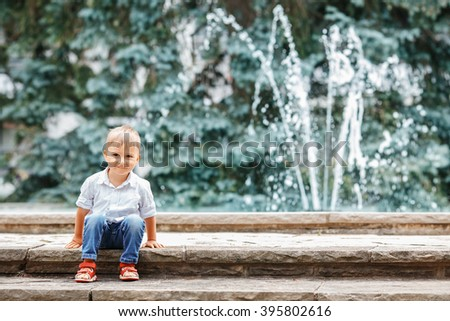 Portrait of cute adorable funny Caucasian  little boy toddler in white shirt and blue jeans playing laughing smiling having fun by fountain in summer outside - stock photo