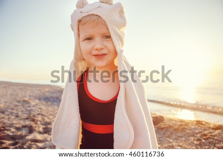Portrait of cute adorable funny happy smiling toddler little girl with towel on beach making poses faces having fun, emotional face expression, lifestyle sunset summer mood, toned - stock photo