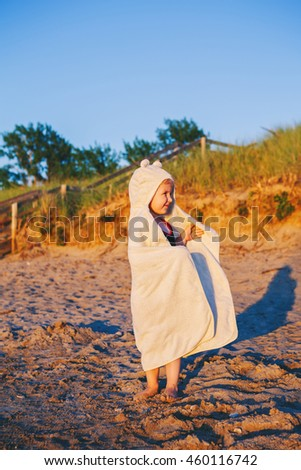 Portrait of cute adorable happy smiling toddler little girl with towel on dunes sand gravel beach having fun, emotional face expression, lifestyle sunset summer mood, toned - stock photo