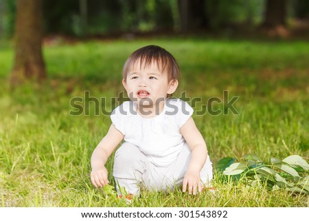 Portrait of cute adorable little Asian girl child baby one year old in white pants shirt, standing on field meadow grass on sunset playing