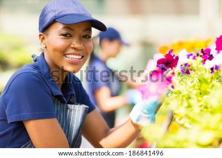 portrait of cute african female florist working in nursery - stock photo