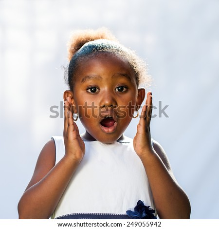 Portrait of cute African girl with shocking face expression.Isolated against light background.