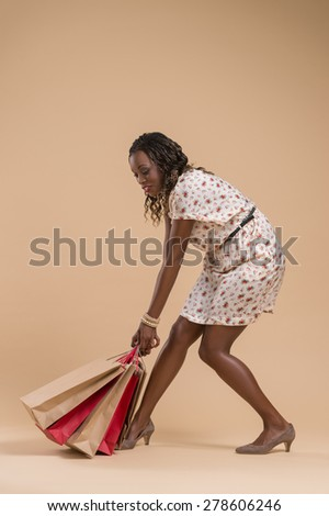 Portrait of cute african woman posing - shopping with very heavy paper bags - stock photo