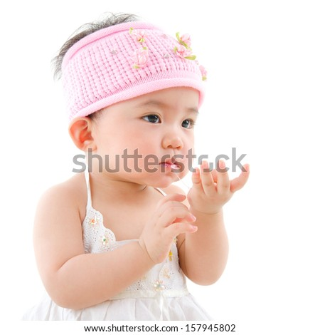 Portrait of cute Asian baby girl  eating,  isolated on white background - stock photo