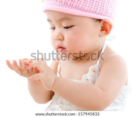 Portrait of cute Asian baby girl eating snack,  isolated on white background - stock photo
