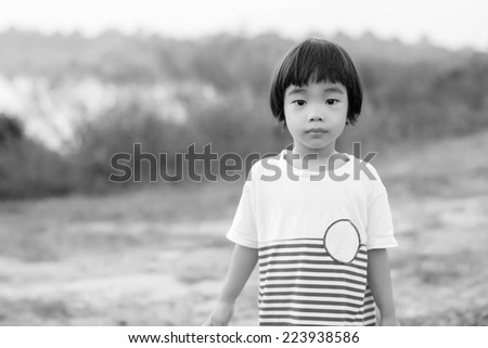 portrait of cute asian boy in the park,monochrome - stock photo