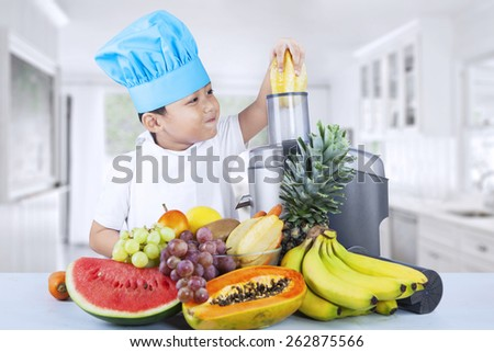 Portrait of cute asian boy is making fruit juice in the kitchen - stock photo