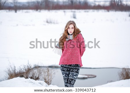 portrait of cute attractive young girl with black and white trousers red sweater freezing on natural background. Winter outdoor photo in cloudy weather  - stock photo