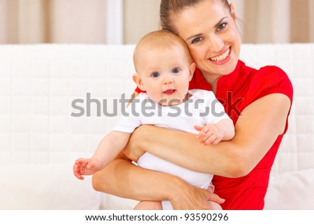 Portrait of cute baby and happy young mother - stock photo
