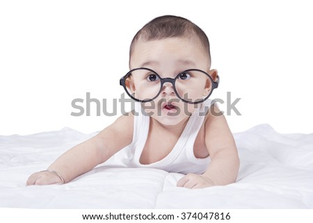 Portrait of cute baby boy lying on the bed while wearing glasses and looking at the camera - stock photo