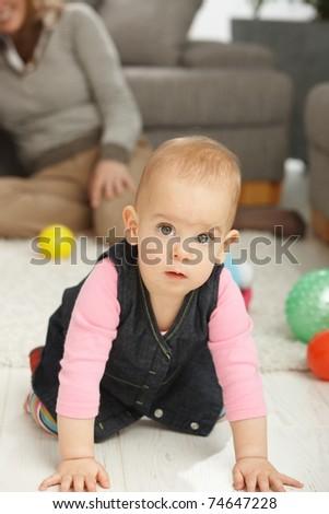 Portrait of cute baby girl kneeling on living room floor looking aside.? - stock photo