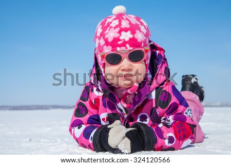 Portrait of cute  baby  girl lying on snow  in winter - stock photo
