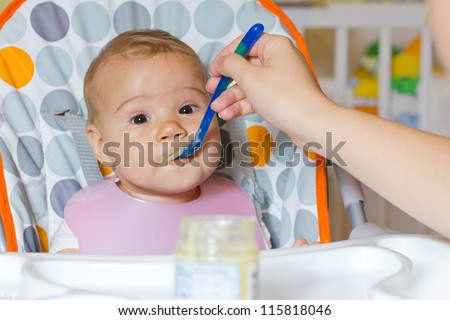 Portrait of cute baby girl while mother feeding.