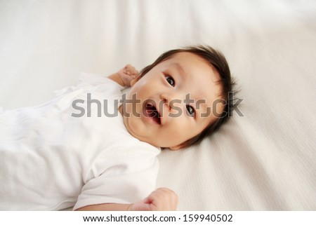 Portrait of cute baby in bed - stock photo