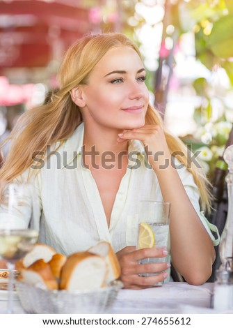 Portrait of cute blond female drink water with lemon in nice outdoor European cafe, healthy lifestyle, enjoying wonderful summer traveling to Italy - stock photo