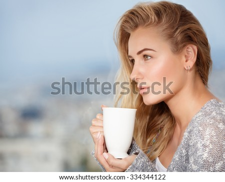 Portrait of cute blond female drinking tea on the outdoors terrace, having breakfast at home, feeling pleasure and relaxation - stock photo