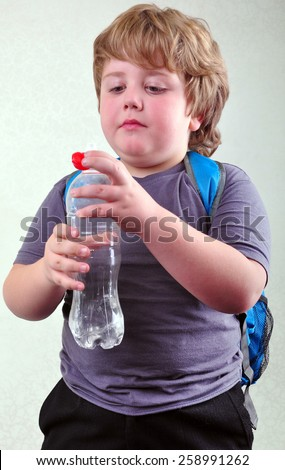portrait of cute blond schoolboy with a bottle of water - stock photo