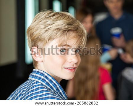 Portrait of cute boy at cinema with family in background - stock photo