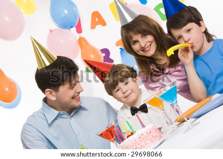 Portrait of cute boy having his birthday party with parents and elder brother surrounding him - stock photo