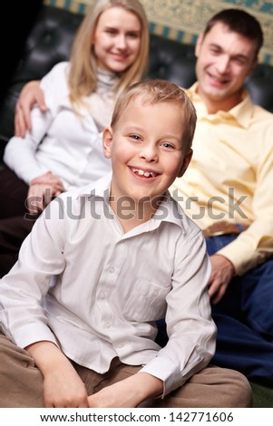 Portrait of cute boy looking at camera with his parents on background - stock photo