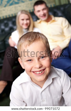 Portrait of cute boy looking at camera with his parents on background