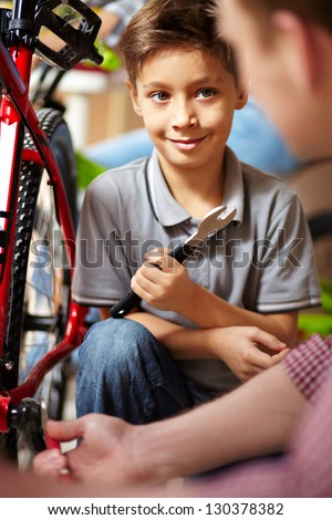 Portrait of cute boy looking at his father while repairing bicycle in garage - stock photo