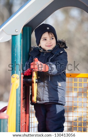 Portrait of cute boy playing in the winter park in sunny day - stock photo