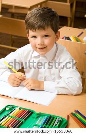 Portrait of cute boy sitting at desk with copybook and colored pencils near by - stock photo