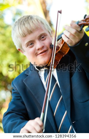 Portrait of cute boy with down syndrome playing violin outdoors. - stock photo