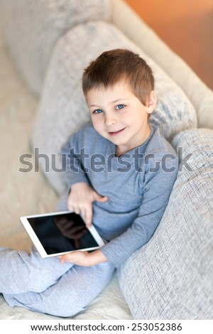Portrait of cute boy with iPad - stock photo